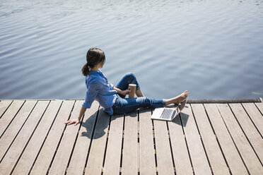 Mature woman sitting on a jetty at a lake, taking a break - MOEF01780