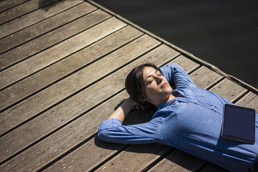 Mature woman taking a break, relaxing on a jetty - MOEF01783