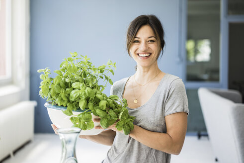 Woman standing in kitchen, holding pot of basil - MOEF01798