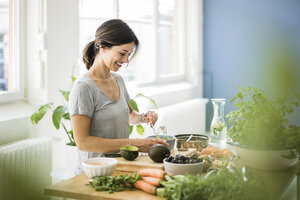 Woman preparing healthy food in her kitchen - MOEF01804