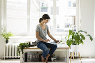 Woman sitting on kitchen table, searching for healthy recipes, using laptop - MOEF01807