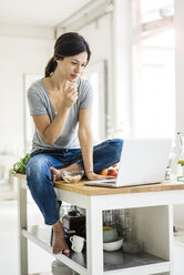 Woman sitting on kitchen table, searching for healthy recipes, using laptop - MOEF01813