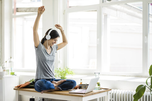 Woman sitting on kitchen table, searching for healthy recipes, using laptop - MOEF01816