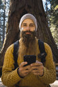 USA, California, Yosemite National Park, Mariposa, portrait of bearded man with cell phone at sequoia tree - KKAF03051