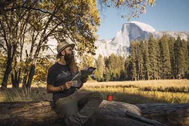 USA, California, bearded man with a map sitting on a log in Yosemite National Park - KKAF03057