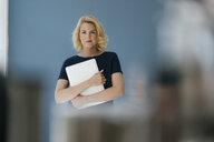 Portrait of blond woman holding laptop - KNSF05391