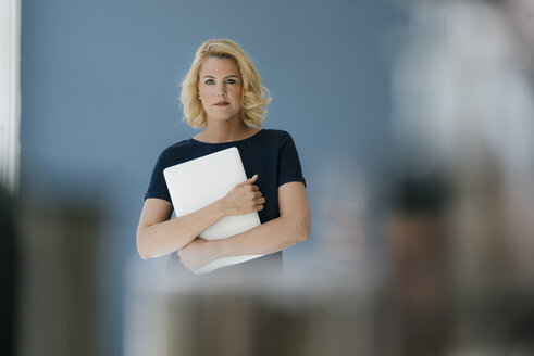 Portrait of blond woman holding laptop - KNSF05391