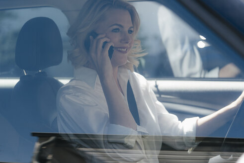 Businesswoman talking on cell phone while driving car - KNSF05397