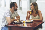 Smiling couple eating and drinking beer in a restaurant on the street - JSMF00595