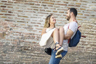 Happy man with backpack carrying girlfriend at brick wall - JSMF00604