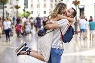 Spain, Andalusia, Malaga, happy couple hugging in the city - JSMF00607