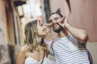 Spain, Andalusia, Malaga, funny man putting his girlfriend's hair as his mustache - JSMF00610