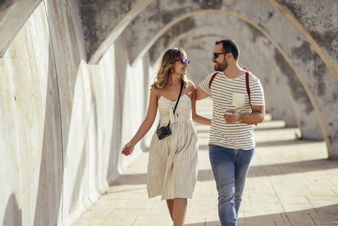 Spain, Andalusia, Malaga, happy tourist couple walking under an archway in the city - JSMF00619