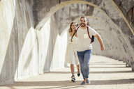 Spain, Andalusia, Malaga, carefree tourist couple running under an archway in the city - JSMF00622