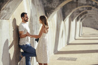 Spain, Andalusia, Malaga, happy affectionate tourist couple under an archway in the city - JSMF00625