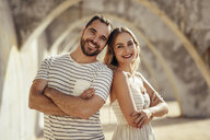 Spain, Andalusia, Malaga, portrait of happy tourist couple under an archway in the city - JSMF00628