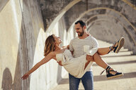 Spain, Andalusia, Malaga, happy man carrying girlfriend under an archway in the city - JSMF00631