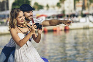 Spain, Andalusia, Malaga, happy tourist couple taking photographs at the harbor - JSMF00637