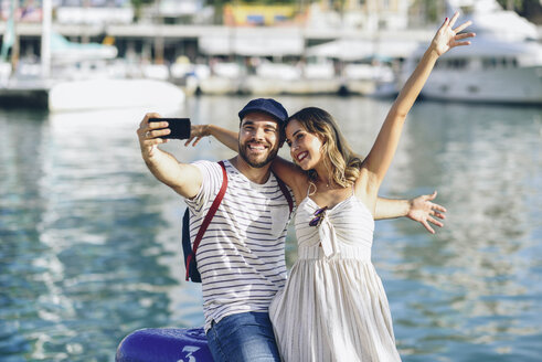 Spain, Andalusia, Malaga, happy tourist couple taking selfie with smartphone at the harbor - JSMF00640