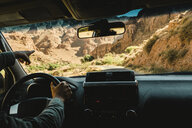 Cropped image of man pointing while driving car against mountains - CAVF57805