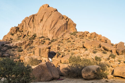 Man climbing on rock against mountains and clear sky at desert - CAVF57811