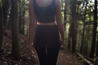 Rear view of midsection woman standing amidst forest - CAVF57826