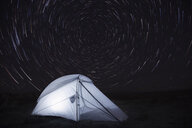 Illuminated tent on field against star trails - CAVF57856
