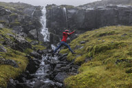 Side view of hiker jumping against waterfall - CAVF57928