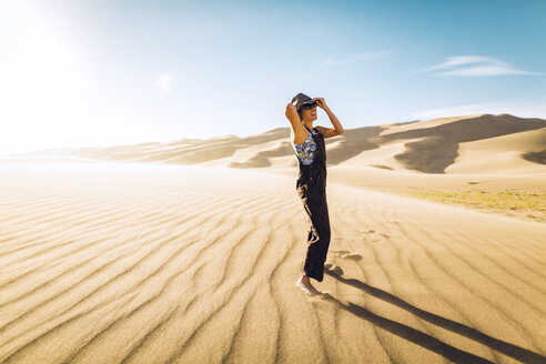 Side view of woman adjusting hat while standing at Great Sand Dunes National Park during sunny day - CAVF57937