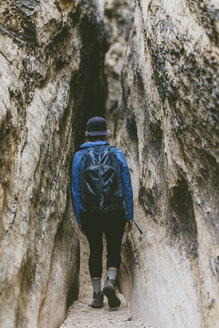 Rear view of female hiker with backpack walking amidst narrow rock formations - CAVF57952