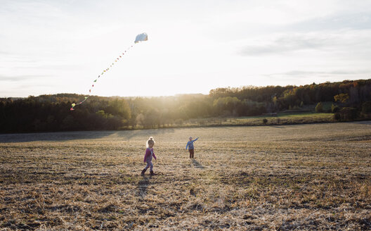 Brother flying kite while sister walking on field against sky - CAVF57958