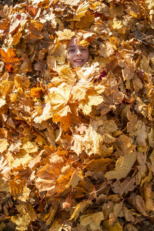 Smiling girl covered with autumn leaves - SARF03998