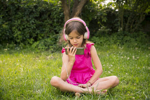 Portrait of girl sitting on a meadow using smartphone and pink headphones - LVF07577