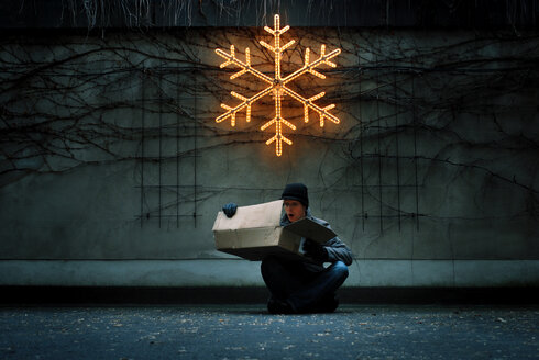 A man sitting down outside under an illuminated star during winter - INGF08604