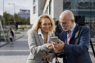 Smiling senior businessman and businesswoman using cell phones in the city - MAUF01777