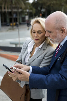 Senior businessman and businesswoman using cell phones in the city - MAUF01780