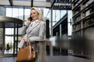 Smiling senior businesswoman talking on cell phone in foyer - MAUF01795