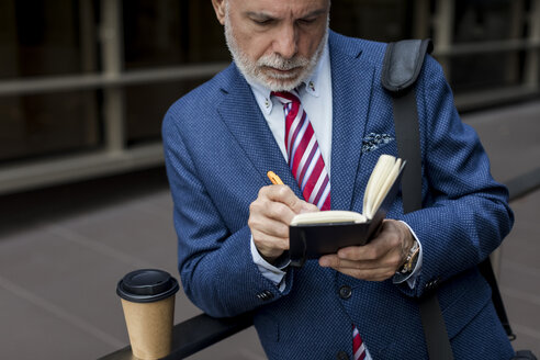 Senior businessman writing in diary outdoors - MAUF01801
