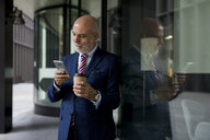 Senior businessman with cell phone and takeaway coffee at glass front - MAUF01807