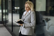 Senior businesswoman leaning against glass front checking diary - MAUF01810