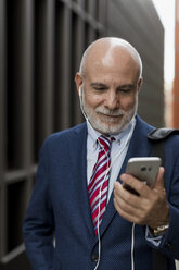 Senior businessman with cell phone and earphones outdoors - MAUF01816
