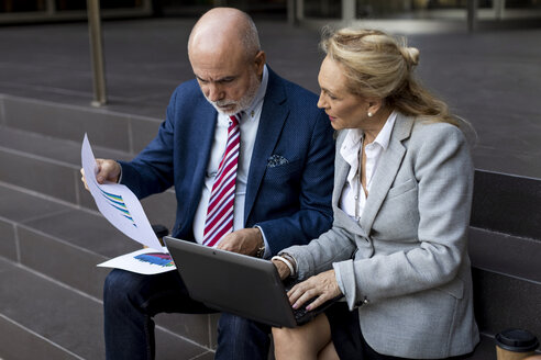 Senior businessman and businesswoman sitting on stairs with laptop and charts - MAUF01822