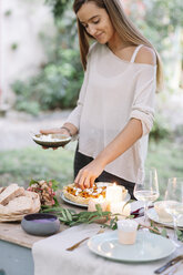 Woman preparing a romantic candlelight meal outdoors - ALBF00709