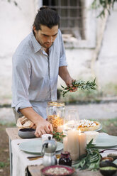 Man preparing a romantic candelight meal outdoors - ALBF00712