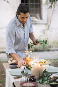 Man preparing a romantic candlelight meal outdoors - ALBF00712
