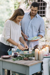 Couple preparing a romantic candlelight meal outdoors - ALBF00715