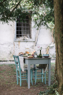 Laid garden table with candles next to a cottage - ALBF00718