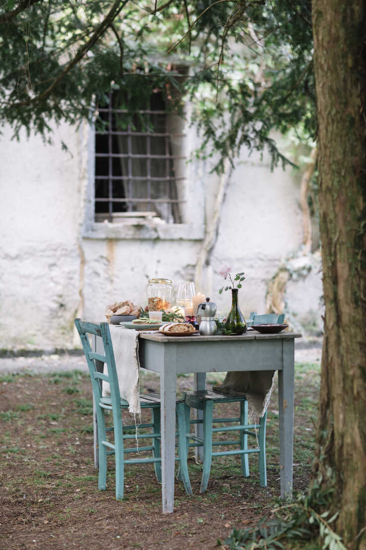 Laid garden table with candles next to a cottage - ALBF00718 - Alberto Bogo/Westend61