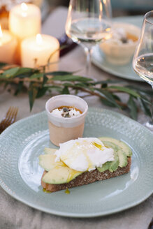 Bread with avocado and dessert on garden table with candles - ALBF00721