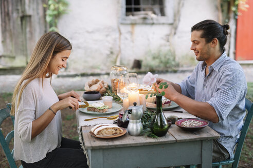 Couple having a romantic candlelight meal next to a cottage - ALBF00730